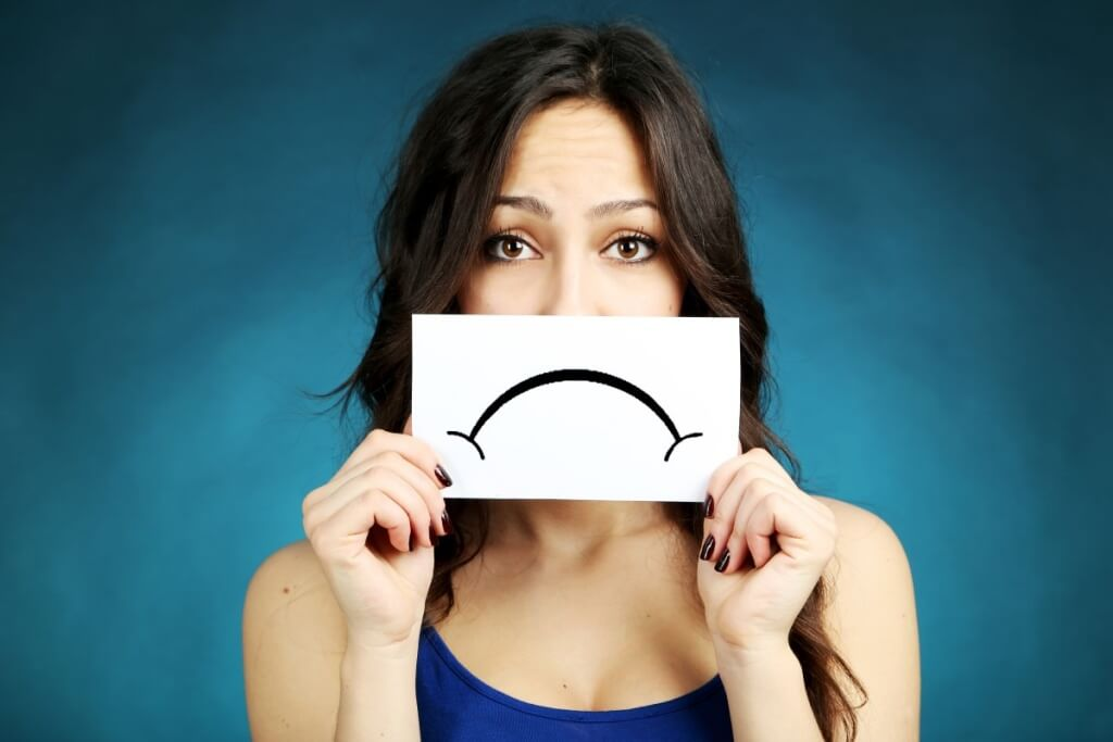 Overcome the Blues of Home Renovation woman showing a sad emoticon on blue background